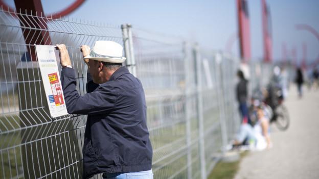 Mann steht an der geschlossenen Grenze zwischen Kreuzlingen und Konstanz.