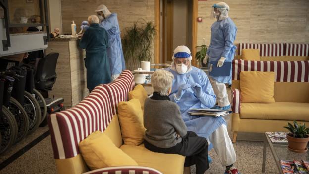 Eine ältere Frau sitzt in einem Altersheim einer Person gegenüber, die in Schutzkleidung gehüllt ist. Rund um sie stehen weitere Personen in Schutzkleidung.