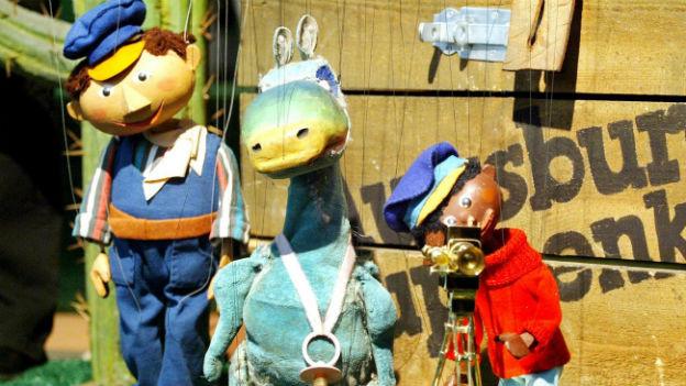 Prominente Figuren aus der Augsburger Puppenkiste: Lukas, der Lokführer; das Urmel und Jim Knopf.