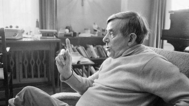 Schwarzweiss Aufnahme von Golo Mann, der in einem Sessel sitzt und mit dem Finger auf etwas zeigt.