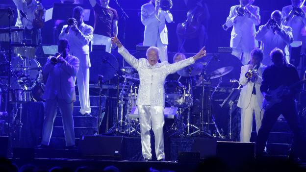 James Last steht vor seinem Orchester und hebt die Arme hoch, um das Publikum anzufeuern.