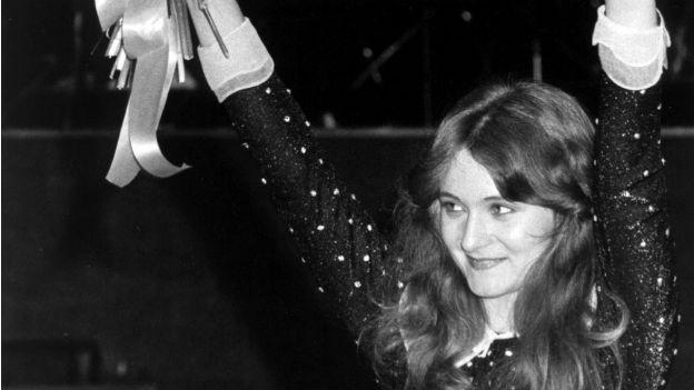 Schwarzweiss Foto von Sängerin Nicole. Sie hebt jubelnd ihre Arme nach dem Sieg am Concours d'Eurovision.