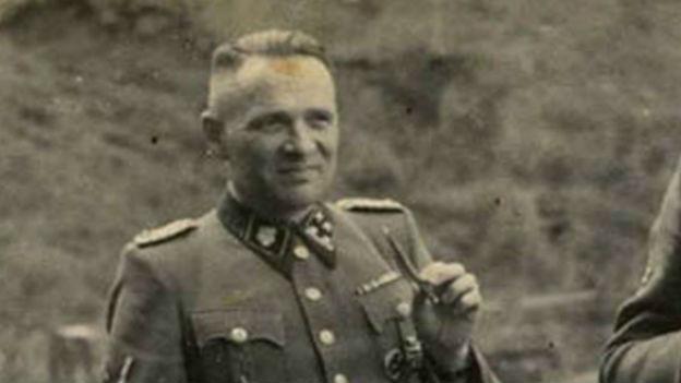 Schwarzweiss Foto von Rudolf Höss in Uniorm, in der linken Hand hält er eine dünne Zigarre.