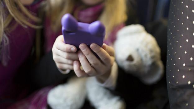 Das Mädchen hält ein Computerspiel in der Hand, im Arm hat sie einen Teddybär.
