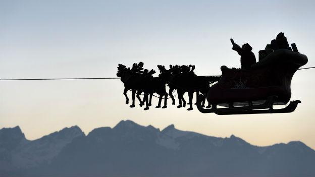 Weihnachtsmann in seiner Kutsche in luftiger Höhe.