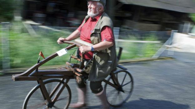Ein älterer Herr fährt auf einer Draisine, einer Art Holz-Fahrrad ohne Pedale.