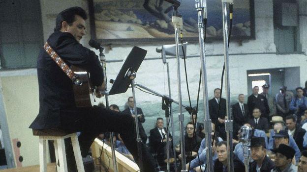 Aufnahme von Johnny Cash in Folsom Prison: Er sitzt auf einem Bar Hocker und spielt auf einer akustischen Gitarre, Häftlinge sehen zu.