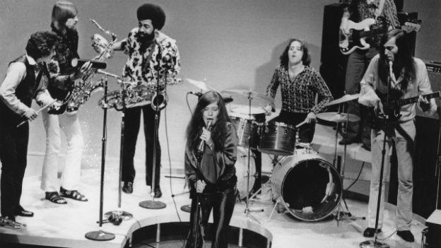 Schwarzweissaufnahme von Janis Joplin und ihrer Band im Hintergrund.