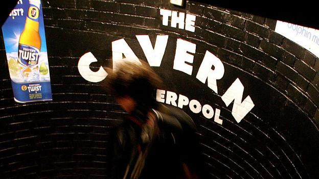 Der Eingang des «Cavern Club» mit Wendeltreppe und Schriftzug, ein Musiker tritt ein