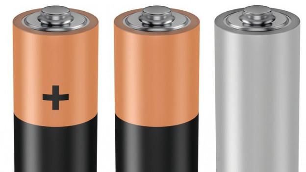 Drei Batterien nebeneinander, so wie man sie heute kennt, zwei sind gold-schwarz, auf der einen ist ein schwarzes Plus, die Batterie ganz rechts ist grau..