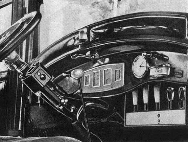 Ein Armaturenbrett eines Autos aus dem Jahr 1925, darauf zu sehen ein eingebautes Autoradio und davor das Steuerrad und der Gangknüppel, die Aufnahme ist schwarzweiss.