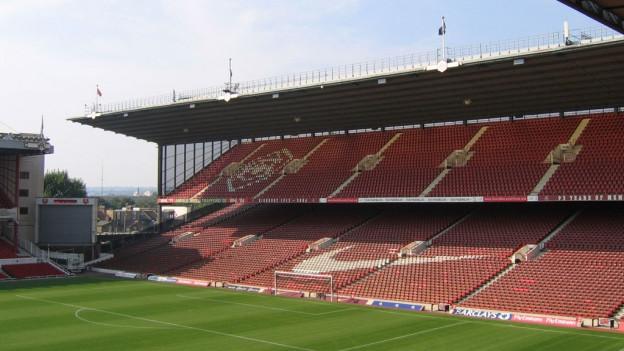 Die Nordtribüne des ehemaligen Arsenal-Stadions in London, die hochgeklappten Sitze sind rot und überdacht, in einem Sektor prangt das goldene Arsenal-Wappen, davor der grüne Rasen..