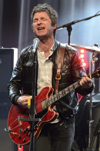 Noel Gallagher am Montreux-Jazz-Festival 2012, er steht mit der Gitarre vor dem Mikrofon, den Mund weit offen, die Augen geschlossen, kurze, dunkle Haare, .