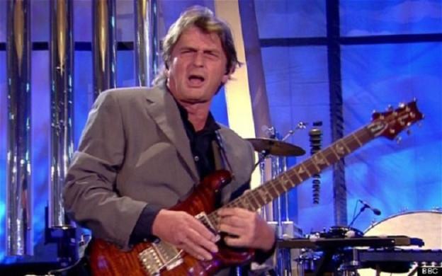 Der Musiker Mike Oldfield bei einem Auftritt 2014, E-Gitarre spielend, den Mund geöffnet und die Augen zusammengekniffen. Die grauen Haare sind zerzaust, er trägt einen blauen Sakko. Im Hintergrund ist das Schlagzeug zu sehen..