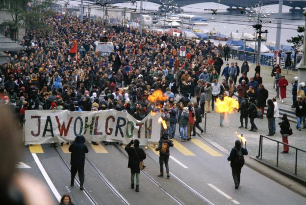 Hausbesetzer des Wohlgroth-Areals in Zürich demonstrieren am 20. November 1993 für ihre Anliegen. Die Menschenmenge trägt ein Banner vor sich her, auf dem «Jawohlgroth» steht.