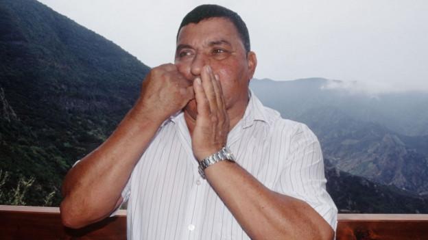 Ein Bewohner La Gomeras benützt die Pfeifsprache El Silbo, er klemmt dabei einen Zeigefinger zwischen die Lippen, hinter ihm die Hügellandschaft der Insel.