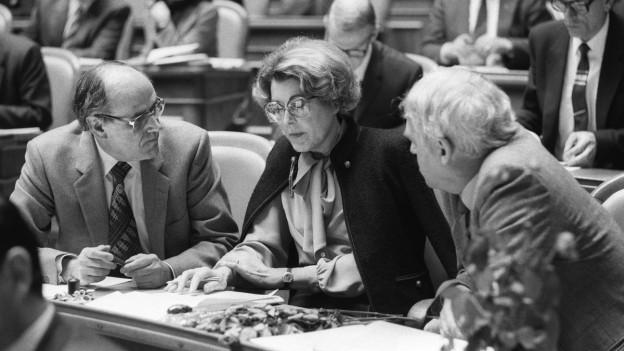 Schwarzweiss Aufnahme von 1983: Lilian Uchtenhagen sitzt an ihrem Arbeitsplatz im Nationalratssaal, Helmut Hubacher (rechts) und Walter Renschler (links) sitzen daneben und blicken zu ihr.
