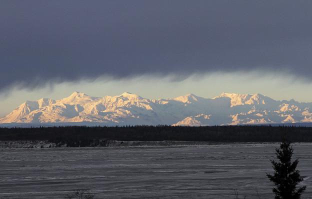 Blick über das Meer auf schneebedeckte Berge in Alaska, Wolken im Hintergrund..