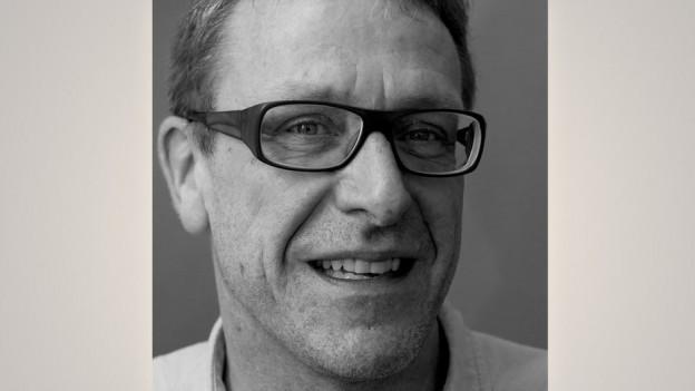 SRF-Nachrichtenredaktor Thomas Fuchs auf einem Schwarzweiss-Portrait, breites Grinsen, kurze Haare und markante Brille.