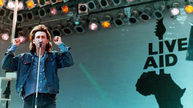 Der Musiker Bob Geldof am Live Aid-Konzert im Londoner Wembley-Stadion 1985, er spricht auf der Bühne ins Mikrofon, beide Hände in der Luft, lange Haare, hinter ihm ist der Live Aid-Schriftzug zu sehen..