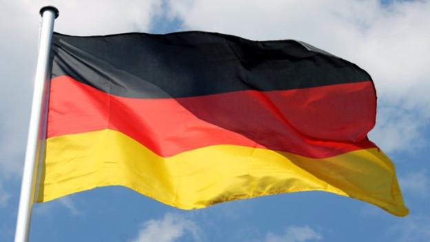 Die deutsche Flagge weht im Wind, im Hintergrund ein Stück Himmel.