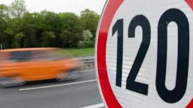 Eine runde Geschwindigkeitstafel mit einer 120 in der Mitte, links davon verschwommen ein vorbeifahrendes Auto.
