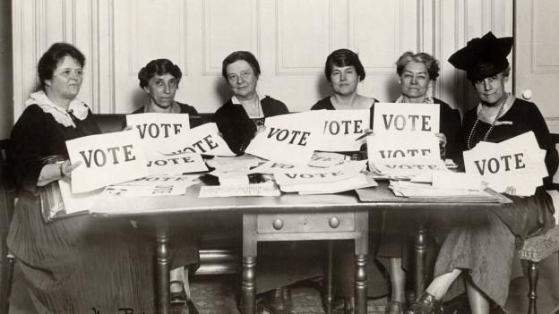 Frauen in Neuseeland auf einer Schwarzweiss-Fotografie, sie sitzen an einem Tisch und halten alle ein Papier mit «Vote» in die Kamera (19. September 1893).