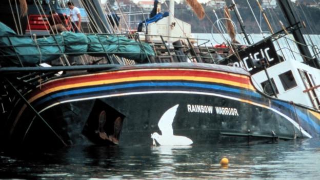 Die «Rainbow Warrior» nach der Bombardierung im Hafen von Auckland, sie liegt auf der Seite (11. Juli 1985).