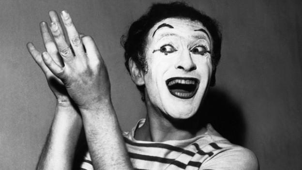 Marcel Marceau bei einem Auftritt in Paris, Schwarzweiss-Aufnahme, sein Gesicht ist weiss geschminkt, er trägt ein Ringelshirt und lacht breit, die Arme auf die rechte Seite ausgestreckt (14. April 1956)