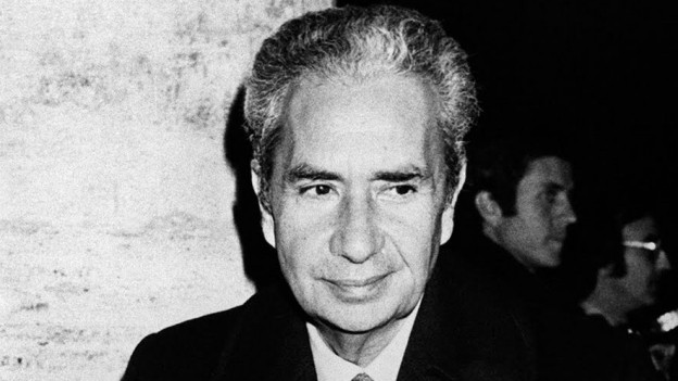 Ein Schwarzweiss-Porträt von Aldo Moro, er lächelt sanft, hohe Stirn, krauses, kurzes Haar.