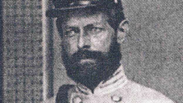 Schwarz-weiss-Foto eines Soldaten in Uniform. Er steht stramm.