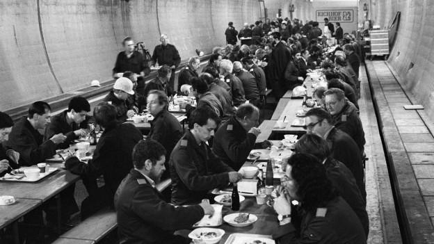 Schwarzweiss-Foto von zahlreichen Zivilschützern, die während der Übung «Ameise» im Luzerner Sonnenbergtunnel zum Essen zusammensitzen (19. November 1987).