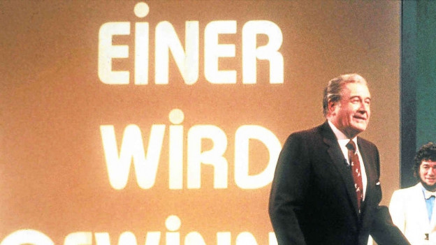 Showmaster Hans-Joachim Kulenkampff mit einem Kandidaten in einer Ausgabe von «Einer wird gewinnen», blauer Anzug, einen grünen Schaumstoffwürfel in den Händen (Aufnahme von 1982).