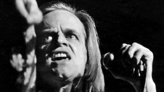 Klaus Kinski bei einer seiner berühmten Jesus-Darstellungen, Schwarzweiss-Foto, wildes Gesicht, lange Haare, er hält mit einer Hand das Mikrofon, mit der anderen zeigt er irgendwo hin (21. November 1971).