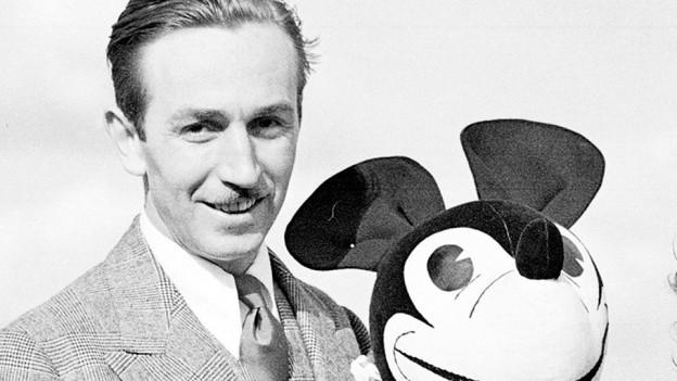 Walt Disney posiert 1935 mit einer Micky Maus-Puppe in London.