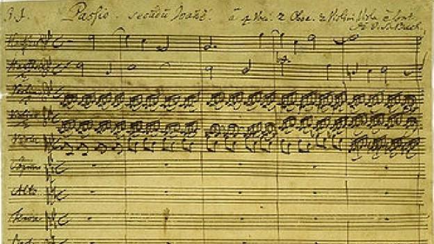 Eine vergilbte Seite mit Noten - die erste Seite aus der Johannespassion.