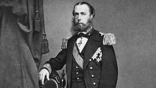 Schwarzweiss-Porträt von Erzherzog Maximilian, die Haare gescheitelt und streng zurückgekämmt, Vollbart, in Uniform auf einen Stuhl gelehnt (Foto von 1864).