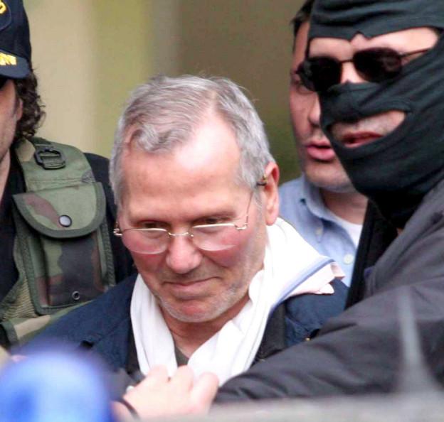 Der Kopf von Bernardo Provenzano, Brille und kurzes weisses Haar, ein leichtes Lächeln auf den Lippen, er wird gerade abgeführt und ist eingerahmt von Polizisten (11. April 2006).