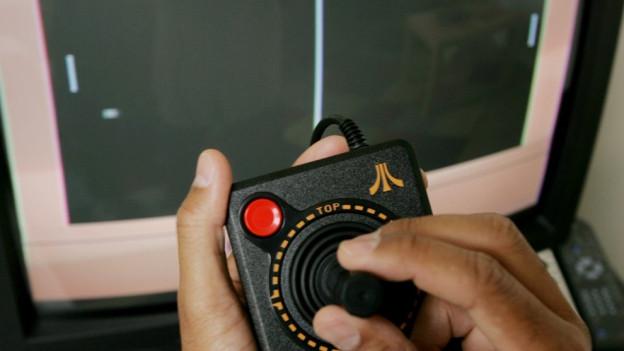 Ein Mann spielt das Spiel «Pong» mit der Atari Flashback 2 Videospielkonsole.