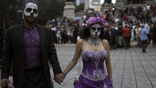Das Bild zeigt ein Paar, das sich für den mexikanischen Tag der Toten geschminkt und verkleidet hat.