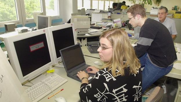 Das Bild zeigt Menschen, die versuchen Probleme mit einem Computervirus zu beheben.