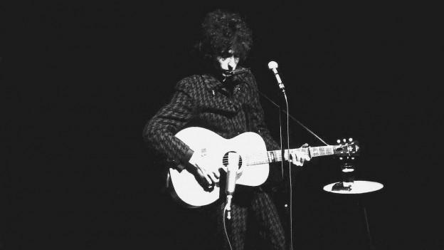 Bob Dylan steht mit einer Gitarre in der Hand auf der Bühne.