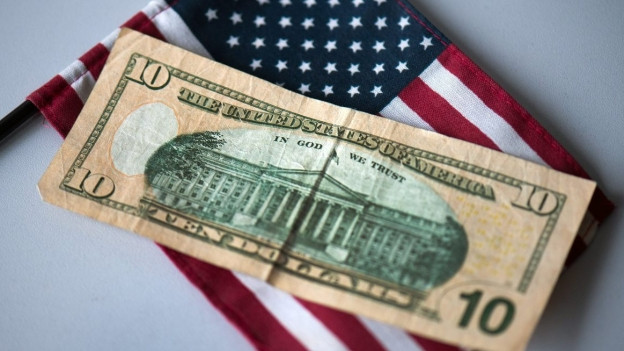 Eine 10-Dollar-Note auf einer US-amerikanischen Flagge.
