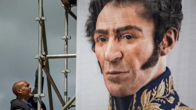 Ein Mann schaut auf ein Portrait von Simón Bolívar