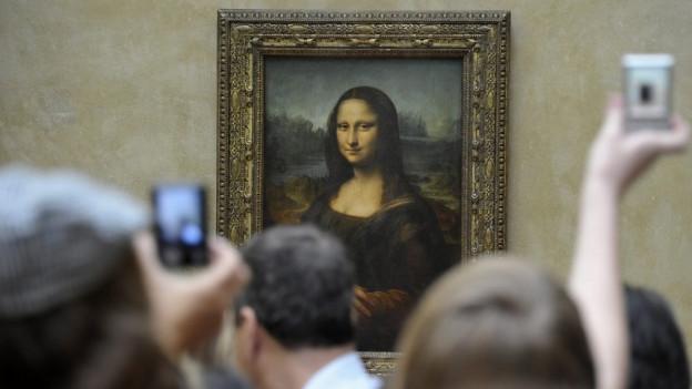 Menschen stehen vor der Mona Lisa und fotographieren das Bild.