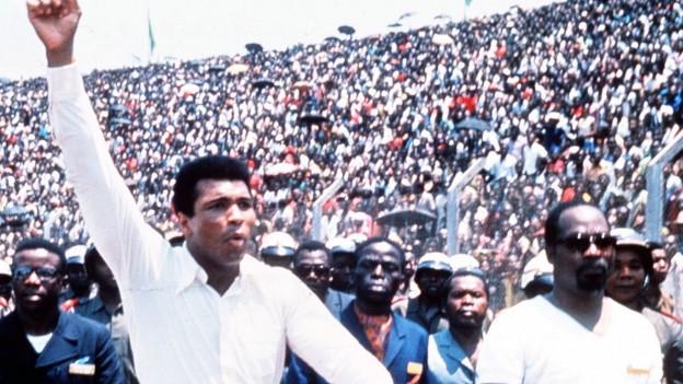 Szenenfoto aus dem Film 'When We Were Kings' zeigt den amerikanischen Boxer Muhammad Ali, links, begleitet von einem Sicherheitsbeamten.