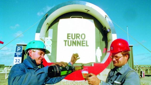 Zwei Arbeiter prosten sich vor dem Portal in Frankreich zu