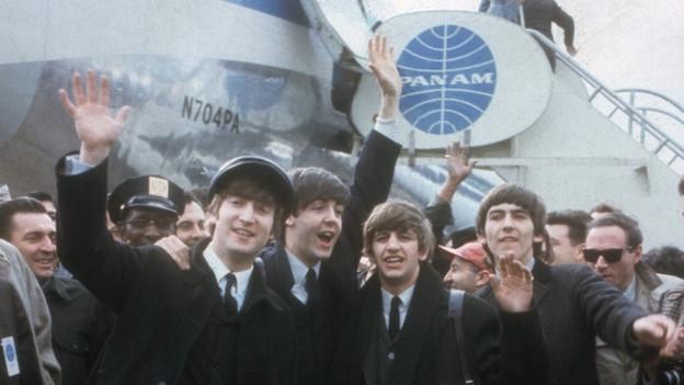Die Beatles vor der PanAm-Maschine, zusammen mit Journalisten