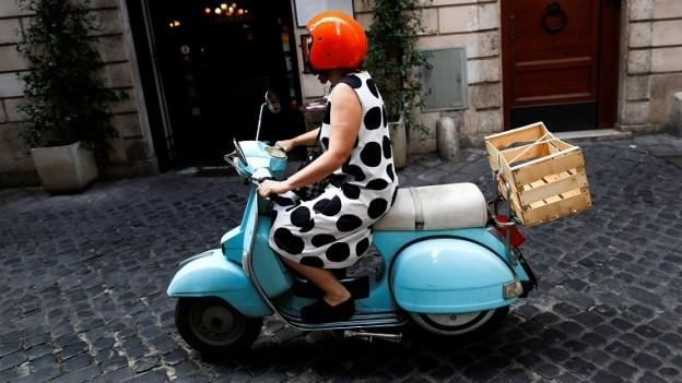Dolce vita: Frau kurvt auf Vespa durch die Römer Innenstadt.