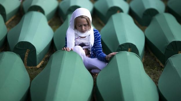 Ein Mädchen kniet vor Särgen der Opfer von Srebrenica